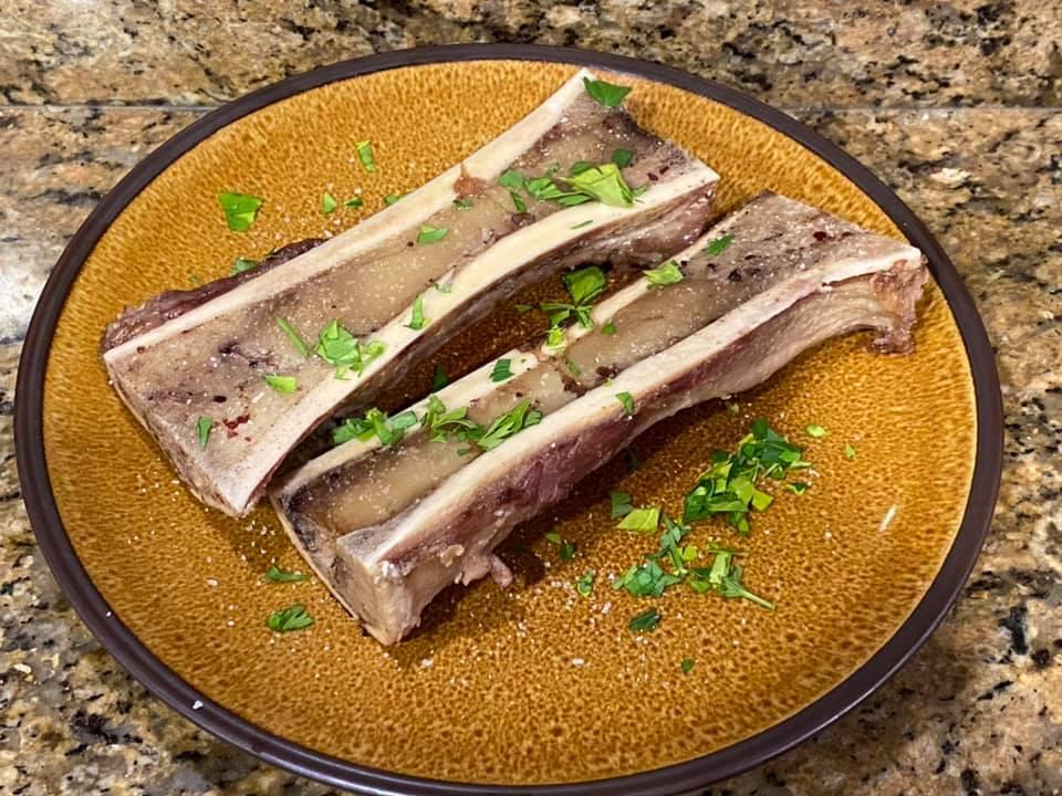 Roasted marrowbones with coarse sea salt and fresh parsley on slice